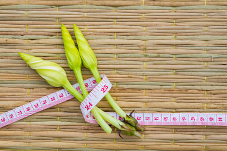 Ipomoea alba L. on traditional mat with measuring tape, diet concept. copyspace