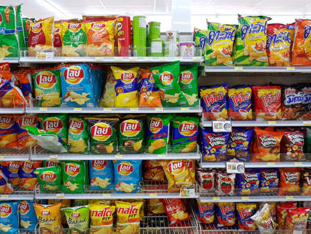 CHIANG RAI, THAILAND - NOVEMBER 26: various brand of potato chips and snacks in packaging for sale on supermarket stand or shelf in Seven Eleven on November 26, 2016 in Chiang rai, Thailand