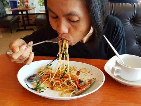BANGKOK, THAILAND - NOVEMBER 30: unidentified woman eating Thai style Spaghetti pasta in Jeffer Steak on November 30, 2016 in BANGKOK, Thailand