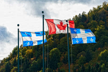 Canadian and the Quebec flag in autumn setting on a cloudy day