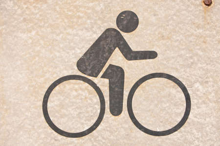 A symbol, people are cycling. On background