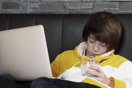 young men fall asleep in front of his notebook while learning and drinkin a glass of water
