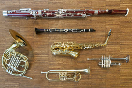Photo pour several wind instruments laying on a wooden floor. trumpet, horn, saxophone, clarinet, flute,  bassoon, curtal - image libre de droit
