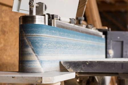 fixed vertical electric belt sander of carpenter in hall