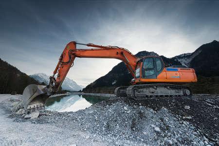 Photo pour big shovel excavator standing on gravel stones before lake - image libre de droit