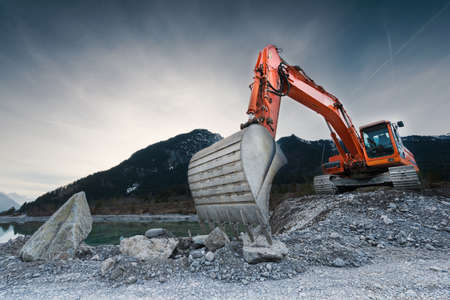 Photo for heavy organge excavator with shovel standing on hill with rocks - Royalty Free Image
