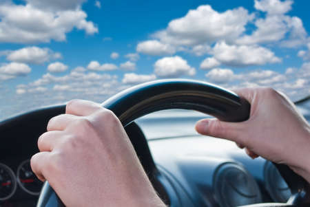 Driver's hands on a steering wheel of a car