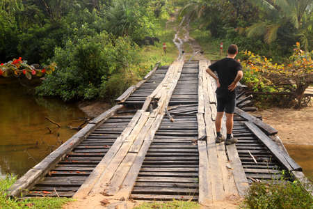 Man assessing the damage in the old wooden bridge