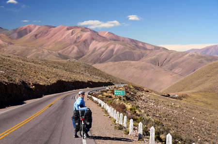 Woman cycling on the empty road in the remote part of north west Argentina
