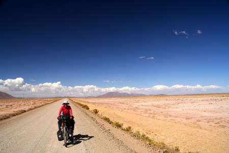 Woman cycling on the remote road in rural part of Bolivia