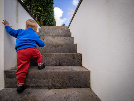 Cute baby boy climbing up the stairs