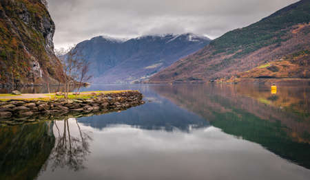 Stunning scenery of norwegian fiord as seen from the shore in small village Flam, Norway