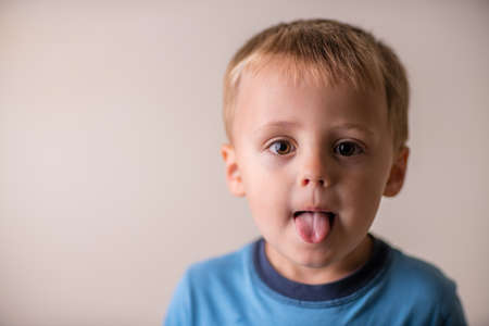 Photo pour Portrait of a cute naughty and mischievous Caucasian boy sticking his tongue out - image libre de droit