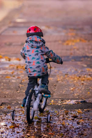 Photo for Little boy wearing red protective helmet riding on a bicycle in the evening after rain - Royalty Free Image