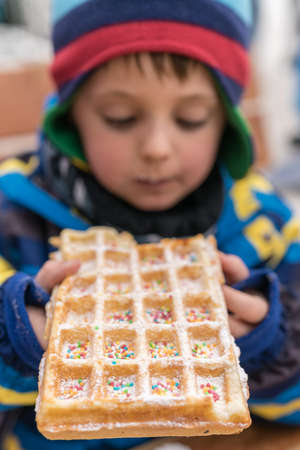 Little boy eating sweet waffle bought from a dessert stand in winter