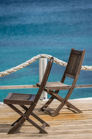 Wooden chairs on a deck platform in Agios Nikolaos beach on Zakynthos Island, Greece