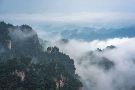 Photo pour Low morning clouds engulfing stone pillars of Tianzi mountains in Zhangjiajie National park, a famous tourist attraction, Wulingyuan, Hunan Province, China - image libre de droit