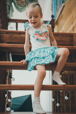 Photo pour a little blond girl in a white and blue dress in polka dots and light socks descends a wooden ladder crawling - image libre de droit