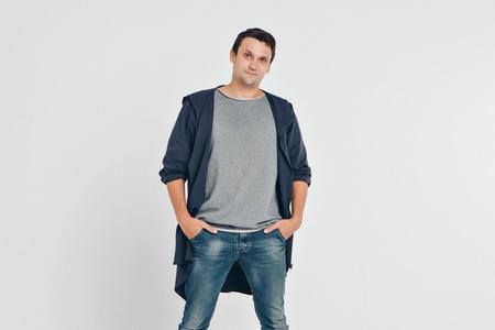 Photo pour handsome man shows off gray clothes on white background - image libre de droit