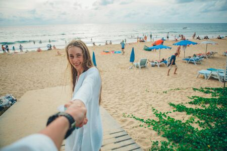 Photo pour Follow me - happy young woman behind her back the guy's hand on the beach. tourists walk by the sea - image libre de droit