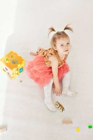 Photo pour portrait of a little girl with tails on white background. Baby plays with toys - image libre de droit