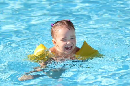 girl in armrests for swimming on vacation in the pool. The concept of Spa, swimming lessons, vacations, water treatment