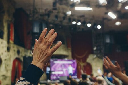 Photo pour hands raised in the crowd. A group of people stretches out their hands. Bright lighting. personal growth training. Warm-up for the audience - all raised their hands up and reach up - image libre de droit