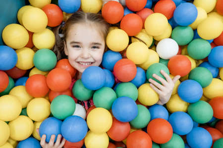 Photo pour a child in the children's playroom. The girl is having fun among the colorful balls. Dry pool party - image libre de droit