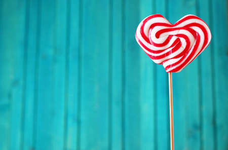 Heart shaped lollipop for Valentine's Day with turquoise background. Copy space background