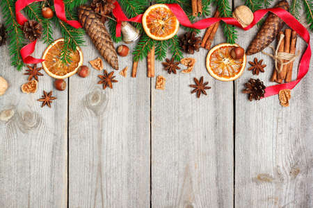 Photo pour Still life, food and drink, seasonal and holidays concept. Christmas decoration with fir tree, oranges, cones, nuts, spices on a wooden table. Selective focus, copy space background, top view - image libre de droit