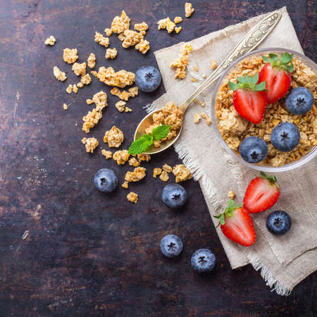 Breakfast, healthy food concept. Homemade muesli granola with berries in a glass on rusty black table. Selective focus, copy space background, top view overhead flat lay