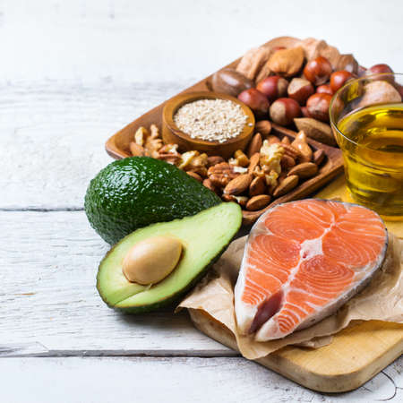 Selection of healthy fat sources food, salmon fish avocado olive oil nuts sesame on a white rustic wooden table