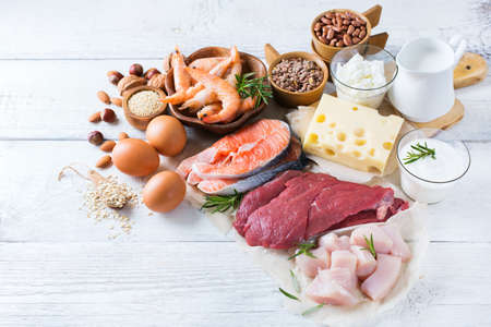 Foto de Assortment of healthy protein source and body building food. Meat beef salmon shrimp chicken eggs dairy products milk cheese yogurt beans quinoa nuts oat meal. Copy space background - Imagen libre de derechos