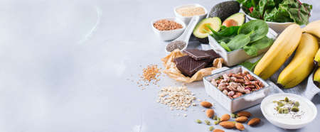 Photo for Healthy food nutrition dieting concept. Assortment of high magnesium sources. Banana chocolate spinach chard, avocado, buckwheat, sesame chia flax seeds, yogurt, nuts, beans oat. Copy space background - Royalty Free Image