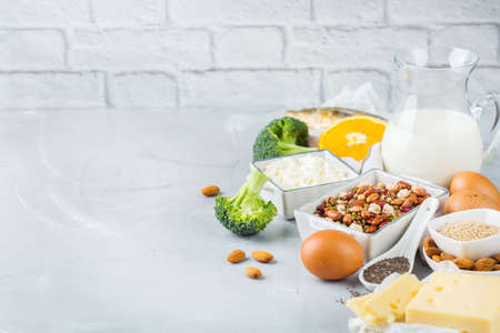 Photo pour Balanced diet nutrition, healthy eating concept. Assortment of food sources rich in calcium, beans, dairy products, sardines, broccoli, chia seeds, almonds on a kitchen table. Copy space background - image libre de droit