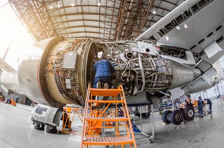 Foto de Specialist mechanic repairs the maintenance of a large engine of a passenger aircraft in a hangar - Imagen libre de derechos