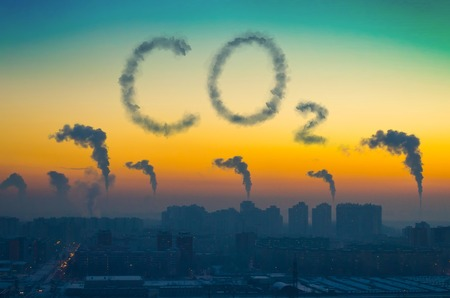 Photo for Evening view of the industrial landscape of the city with smoke emissions from chimneys at sunset. Inscription CO2 - Royalty Free Image