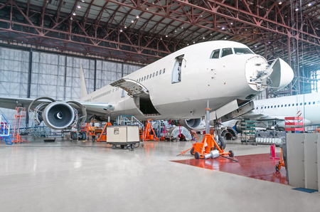 Photo pour Passenger airplane on maintenance of engine and fuselage repair in airport hangar. Aircraft with open hood on the nose and engines, as well as the luggage compartment - image libre de droit