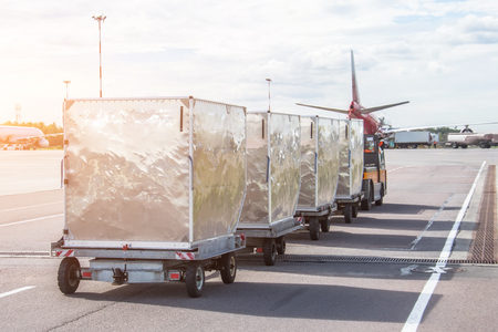 Foto de Trailers with containers of onboard aviation food for loading into a passenger airplane. - Imagen libre de derechos