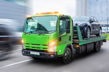 Photo for Passenger car loaded onto a tow truck for transportation, delivered to the destination. With motion blur speed effect - Royalty Free Image