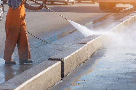 Photo pour Worker cleaning driveway with gasoline high pressure washer splashing the dirt, asphalt road border. High pressure cleaning - image libre de droit