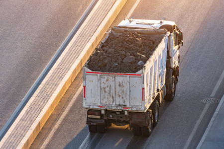 Photo for Truck loaded with soil in the back is on the side of the highway - Royalty Free Image