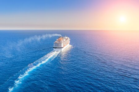 Photo pour Cruise ship liner goes into horizon the blue sea leaving a plume on the surface of the water seascape during sunset. Aerial view, concept of sea travel, cruises - image libre de droit