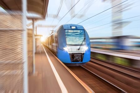 Electric train at high speed rides past the passenger platform station in the city