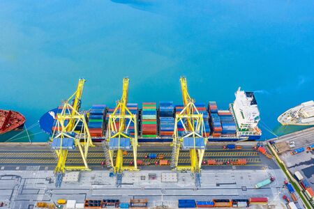 Foto de Large cargo ship maritime at the port is moored at the port, cranes load cargo from trucks delivering containers, aerial top view from high - Imagen libre de derechos