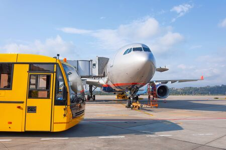 Shuttle yellow bus waiting for passengers on the plane for transportation to the airport terminal. Aircraft arrival background. Travel tourist destination concept