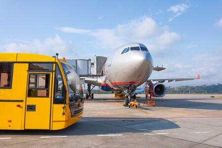 Foto de Shuttle yellow bus waiting for passengers on the plane for transportation to the airport terminal. Aircraft arrival background. Travel tourist destination concept - Imagen libre de derechos