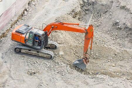 Photo pour Red excavator digs rocky soil, top view - image libre de droit
