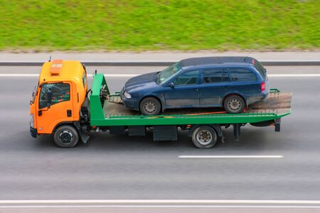 Photo for Tow truck carries an evacuated car on a highway, aerial view - Royalty Free Image