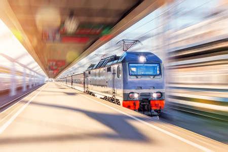 Photo pour The lead electric locomotive with a passenger train passes at high speed through the city platform - image libre de droit